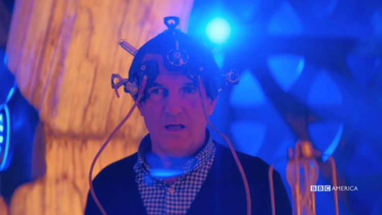 "Doctor Who:  ""Can You Hear Me?"" screen shot Graham in the TARDIS with a contraption on his head"