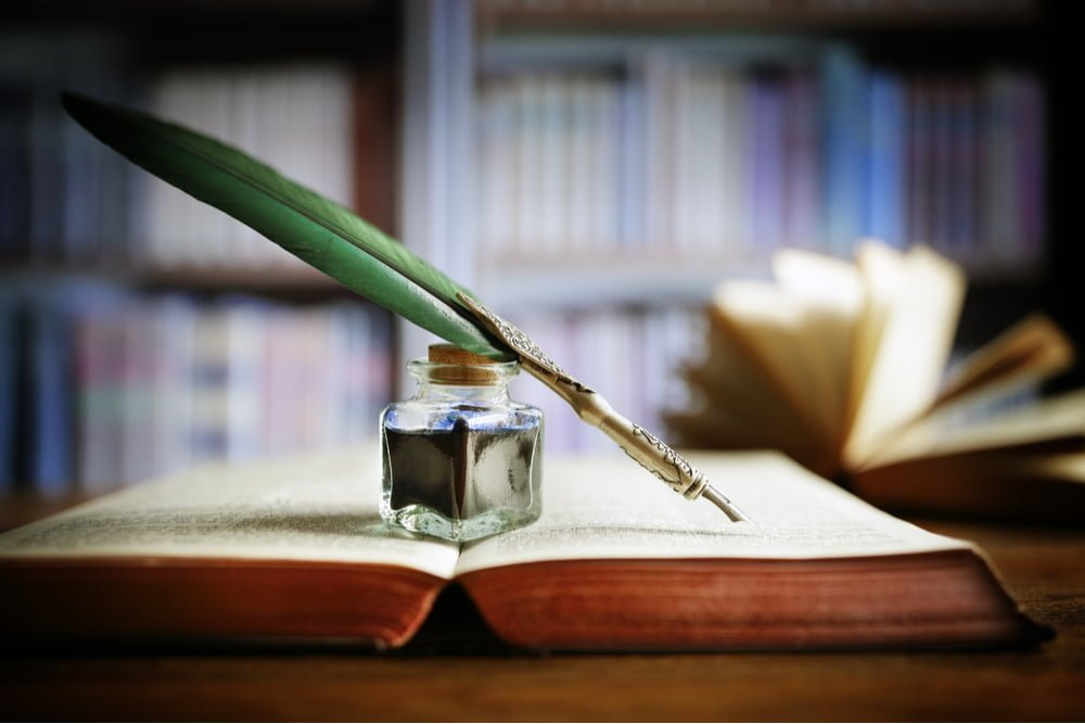 open book with green quill and ink jar